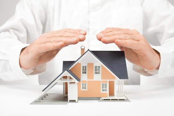 problème installation : main au dessus d'une maison symbolisant la protection d'une installation d'énergie photovoltaique pour une maison